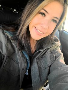 Image Description: A selfie of a young woman in a black jacket smiling at the camera
